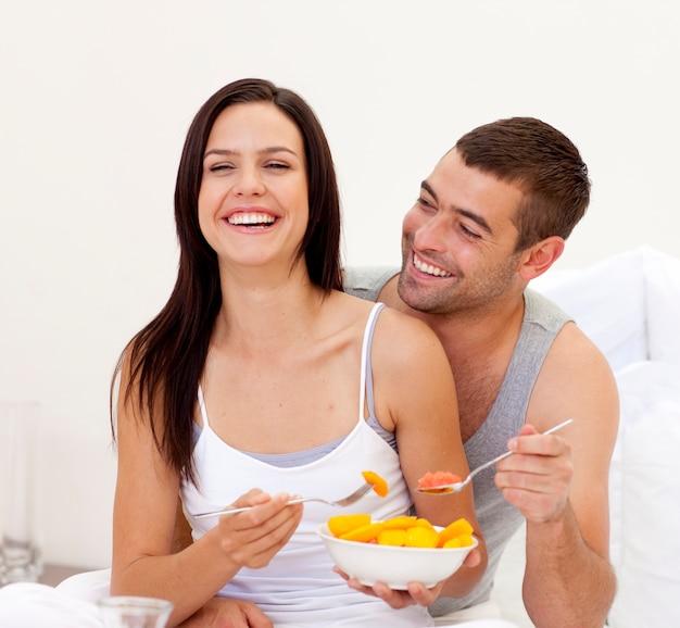 Coppie sorridenti che mangiano prima colazione nutriente a letto