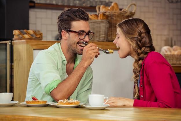 Coppie sorridenti che mangiano torta