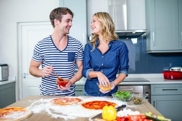 Coppie sorridenti che preparano pizza in cucina