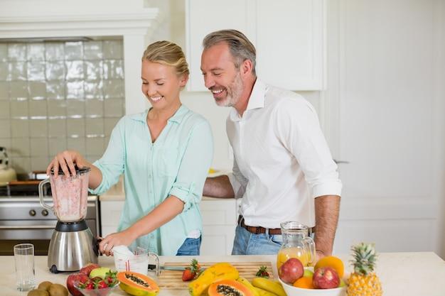Coppie sorridenti che preparano succo fresco in cucina