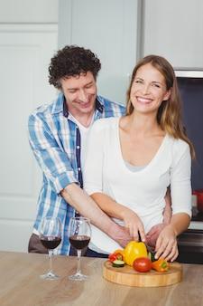 Coppie sorridenti che preparano un'insalata di verdure