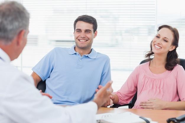 Coppie sorridenti che prevedono medico consultantesi del bambino