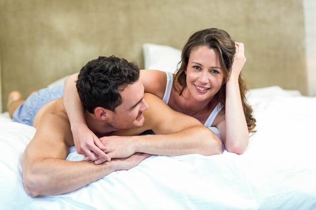 Coppie sorridenti che si trovano a letto insieme