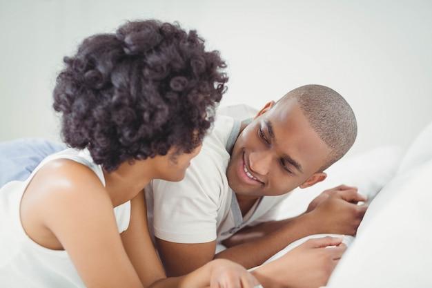 Coppie sorridenti che si trovano sulla conversazione del letto