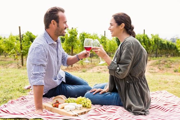 Coppie sorridenti che tostano i bicchieri di vino rossi