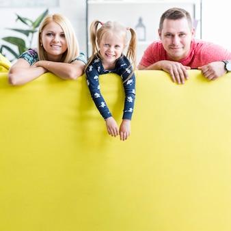 Coppie sorridenti con il bambino che si siede sul sofà