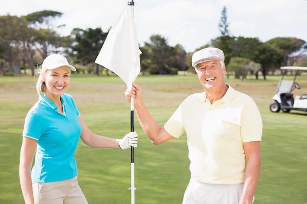 Coppie sorridenti del giocatore di golf che tengono bandiera bianca