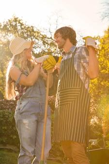 Coppie sorridenti nel giardino che tiene un rastrello