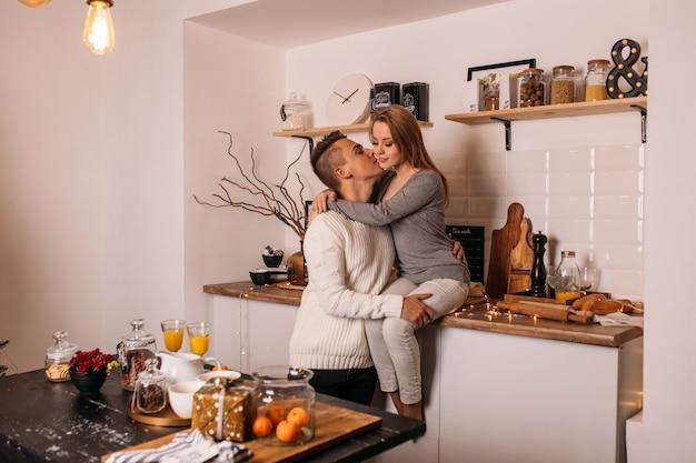 Coppie sorridenti nell'amore in cucina a casa