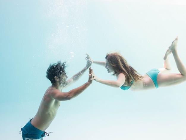 Coppie sorridenti sotto l'acqua che un le mani