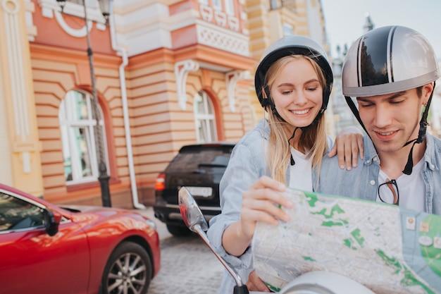 Coppie splendide che guidano un motociclismo nella città e che guardano una mappa