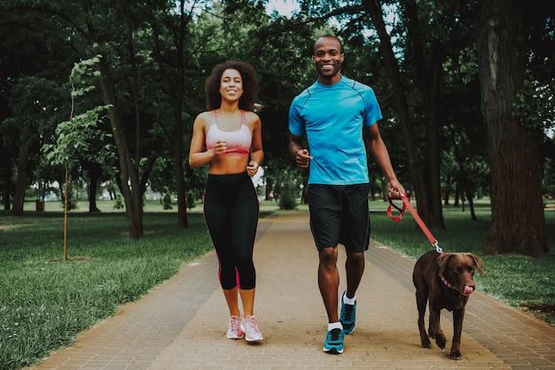 Coppie sportive felici e cane sveglio marrone.