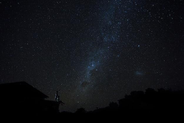 Coppie sul tetto che guardano modo mliky e stelle nel cielo notturno