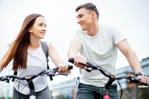 Coppie sulle bici all'aperto che sorridono