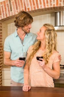 Coppie sveglie che abbracciano e che godono di un bicchiere di vino nella cucina