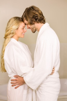 Coppie sveglie che abbracciano nell'accappatoio nel bagno a casa