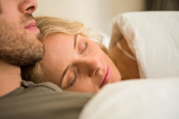 Coppie sveglie che dormono sul loro letto nella camera da letto