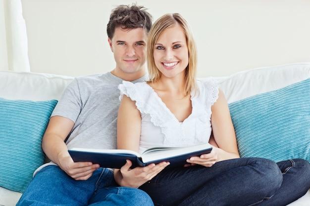 Coppie sveglie che leggono insieme un libro che si siede sullo strato a casa