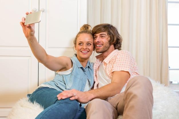 Coppie sveglie che prendono un selfie con lo smartphone nel salone
