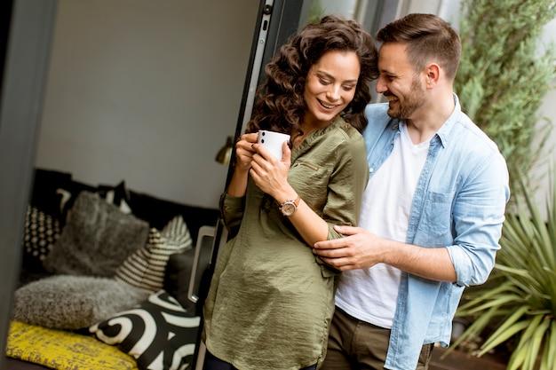 Coppie sveglie felici nell'amore che si abbracciano e che bevono caffè