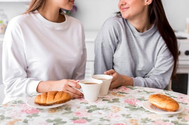 Coppie teenager che bevono caffè al tavolo