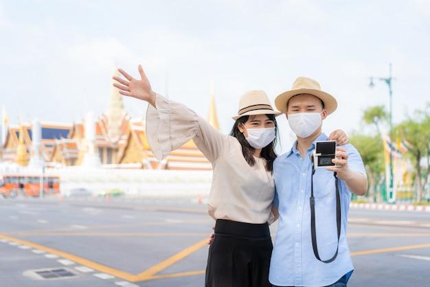 Coppie turistiche asiatiche che indossano una maschera protettiva