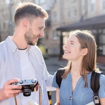 Coppie turistiche sveglie all'aperto con la macchina fotografica