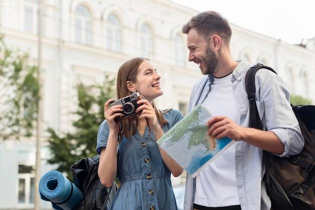 Coppie turistiche sveglie con la mappa e la macchina fotografica