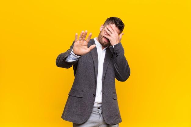 Coprendo il viso con la mano e mettendo l'altra mano in avanti per fermare la fotocamera, rifiutando foto o immagini