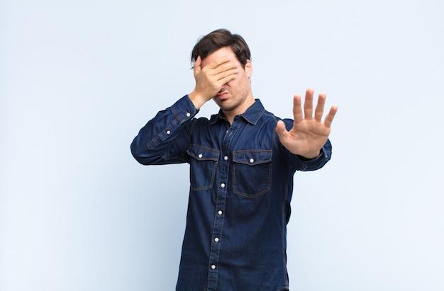 Coprendo il viso con la mano e mettendo l'altra mano in avanti per smettere di rifiutare foto o immagini