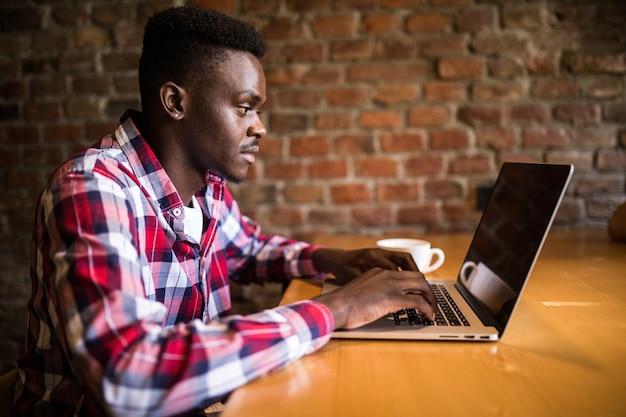 Copywriter afroamericano giovane alla moda positivo che chiacchiera sul computer portatile