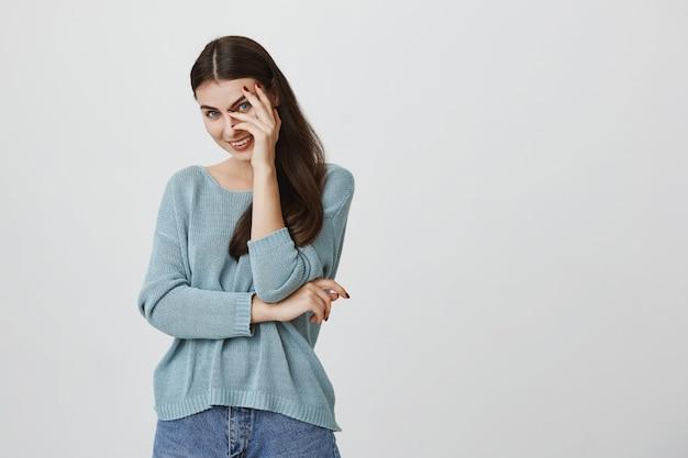 Coquettish attraente donna copre gli occhi dietro la mano e ridacchia, sorridendo