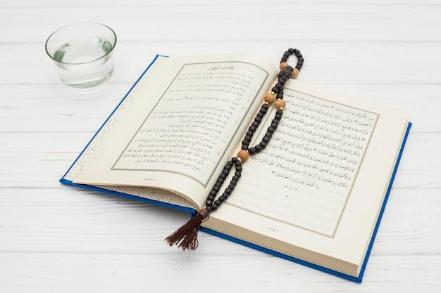 Corano con perle di rosario e acqua nella ciotola