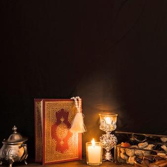 Corano e candele vicino dolce