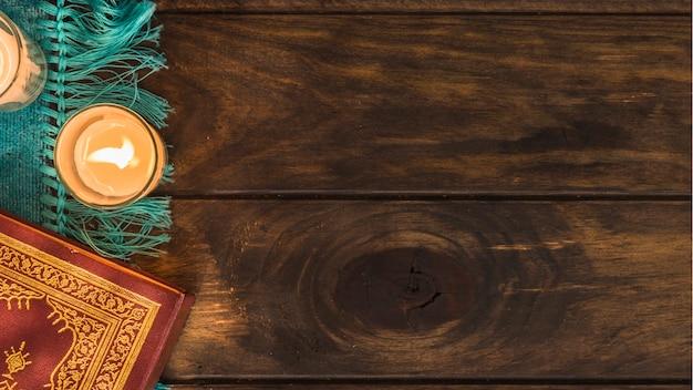 Corano sdraiato vicino a candele fiammeggianti