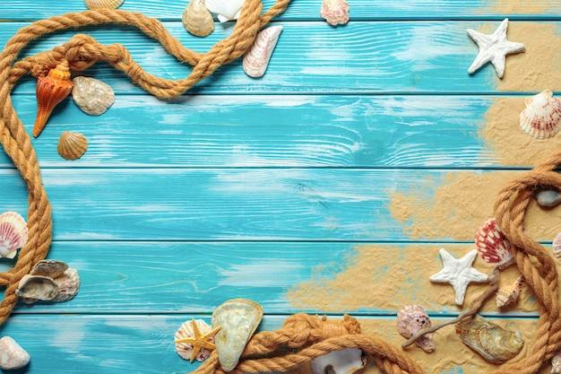 Corda del mare con le conchiglie sulla sabbia di mare