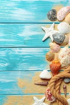 Corda del mare con molte conchiglie differenti sulla sabbia di mare su un fondo di legno blu nella vista superiore