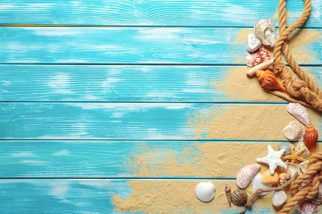 Corda del mare con molte conchiglie differenti sulla sabbia di mare su un fondo di legno blu