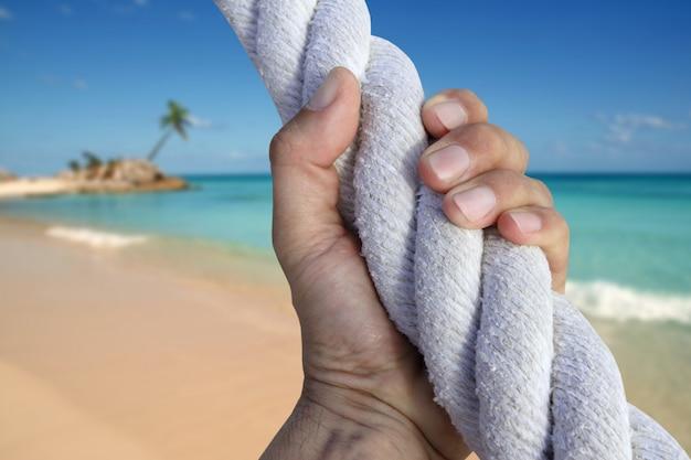 Corda della spiaggia di paradiso di avventura della presa della gru a benna della mano dell'uomo
