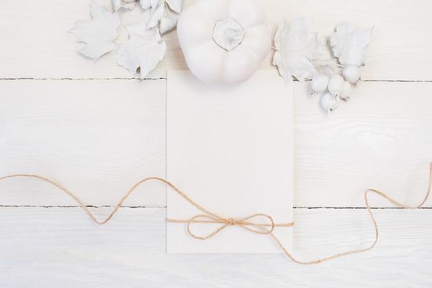 Corda di lino, zucca bianca, bacche e foglie, foglio di carta bianco di autunno su un fondo di legno