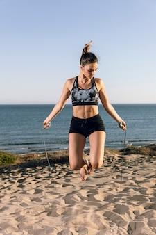 Corda di salto della donna alla spiaggia