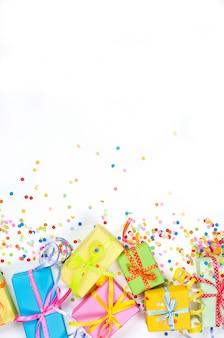 Coriandoli assortiti colorati con serpentina e scatole regalo su bianco