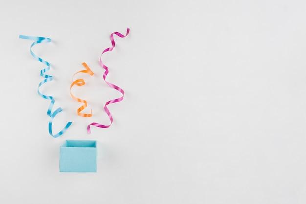 Coriandoli che escono dalla confezione regalo con copia-spazio