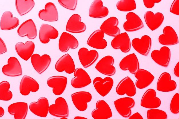 Coriandoli cuori rossi su rosa, concetto di romanticismo