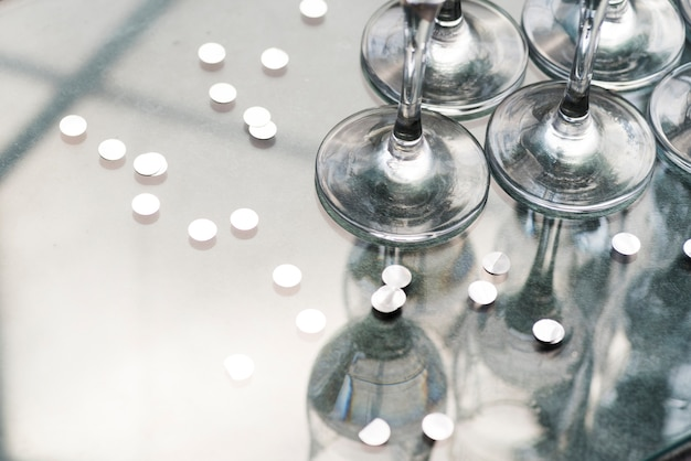 Coriandoli d'argento e riflessione di bicchieri di vino sul tavolo