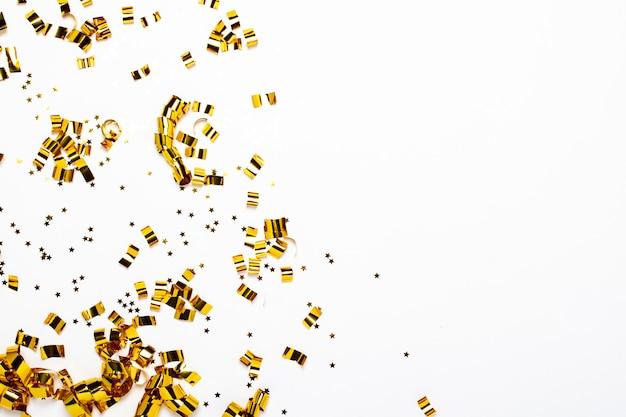 Coriandoli d'oro su uno sfondo bianco. concetto di vacanza, festa, compleanno, decorazione.