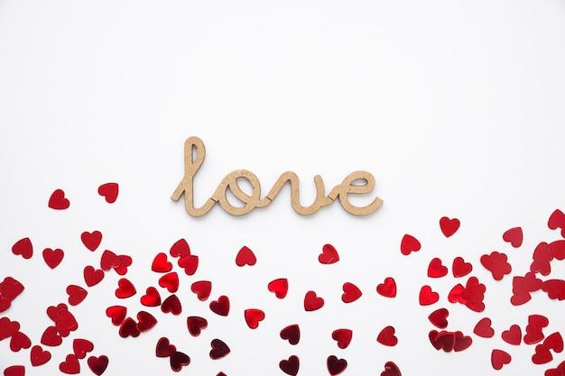 Coriandoli del cuore vicino alla scrittura d'amore