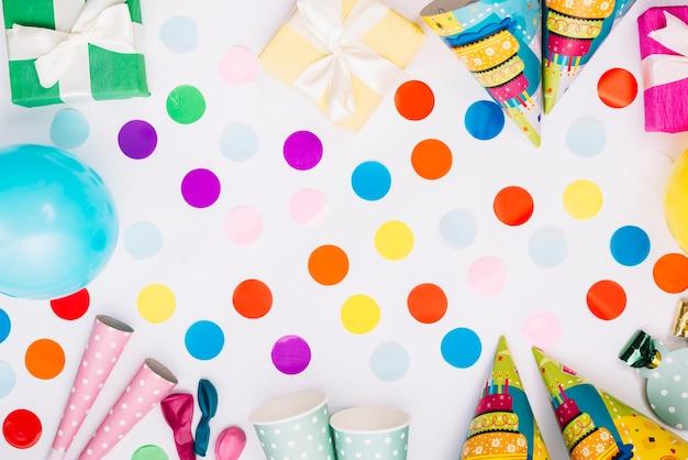 Coriandoli di palloncini con scatole regalo; cappello da festa; corno; tazza usa e getta su sfondo bianco