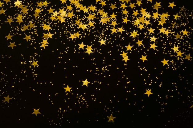 Coriandoli di stelle d'oro e glitter su uno sfondo nero festa di natale capodanno festivo