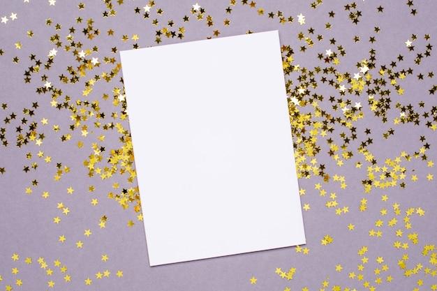 Coriandoli di stelle dorate e carta bianca su gray